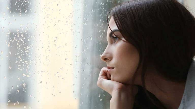 A woman gazing out of a rainy window