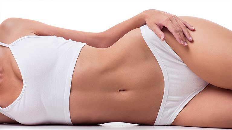 Woman lying on her side revealing her abdomen after SculpSure body contouring treatments