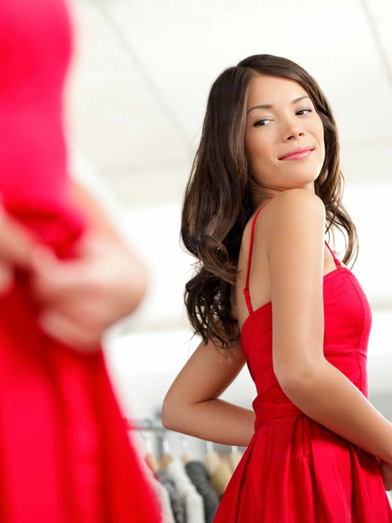 Young woman in red dress looking in a mirror at her profile after SculpSure Body Contouring