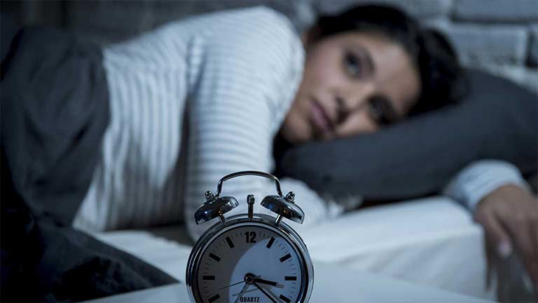 A woman unable to sleep lying in bed staring at her clock